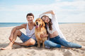 Happy young couple with dog sitting on the beach Royalty Free Stock Photo