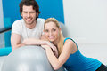 Happy young couple doing fitness training at a gym posing with a large silver gym ball smiling at the camera Stock Photography