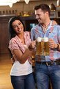 Happy young couple drinking beer in pub clinking glasses smiling Stock Photos