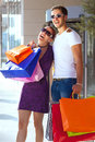 Happy young couple embracing each other having fun during shopping carrying colorful shopping bags Royalty Free Stock Photos