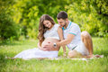 Happy young couple expecting baby, pregnant woman with husband touching belly Royalty Free Stock Photo