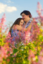 Happy Young Couple in garden of flowers Royalty Free Stock Images