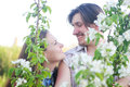 Happy Young Couple in garden of flowers Royalty Free Stock Photo
