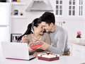 Happy young couple with gift boxes in the kitchen in home Stock Photo