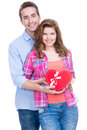Happy young couple with a gift in studio isolated on white background Stock Photography