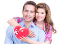 Happy young couple with a gift in studio isolated on white background Stock Images