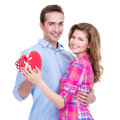 Happy young couple with a gift in studio isolated on white background Royalty Free Stock Image