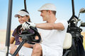 Happy young couple on golf course smiling and driving in buggy in Royalty Free Stock Image