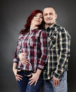Happy young couple on gray background studio shot Royalty Free Stock Photo