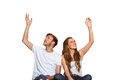 Happy young couple with hands raised over white background Royalty Free Stock Image