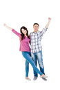 Happy young couple with hands raised standing over white background Stock Image