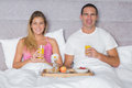 Happy young couple having breakfast in bed smiling at camera at home bedroom Stock Photo