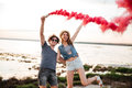 Happy young couple having fun with smoke bomb in hand Royalty Free Stock Photo