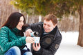 Happy young couple having fun in the winter park drinking hot tea Royalty Free Stock Image