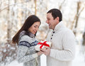 Happy young couple having fun in the winter park love with present Stock Photo