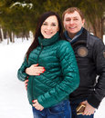 Happy young couple having fun in the winter park pregnant Stock Photo