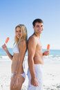 Happy young couple holding ice creams smiling at camera the beach Royalty Free Stock Photos