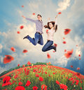 Happy young couple jumping in poppies field into the sky over Stock Image