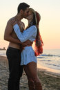 Happy young couple kissing at the beach at dusk in their twenties tenderly embracing and just before sunset Royalty Free Stock Images