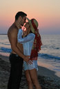 Happy young couple kissing at the beach at dusk in their twenties tenderly embracing and in wet clothes just before sunset Stock Photo