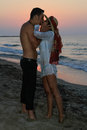 Happy young couple kissing at the beach at dusk in their twenties tenderly embracing and in wet clothes just before sunset Royalty Free Stock Image