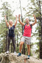Happy young couple looking at camera with raised hands in the nature Royalty Free Stock Images