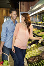 Happy young couple looking at each other while shopping for vegetables in market Stock Images
