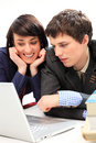 Happy young couple looking at laptop. Stock Photo