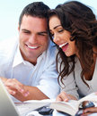 Happy young couple looking at laptop Stock Images