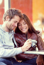 Happy young couple looking at pictures on camera beautiful lovers having fun together outside photos vintage Royalty Free Stock Images