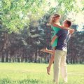Happy young couple in love enjoys spring day, loving man holding on hands his woman carefree walking in park