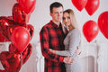 Happy young couple in love posing with red heart balloons