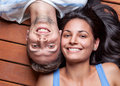 Happy young couple lying on a wooden floor head to head Royalty Free Stock Photography