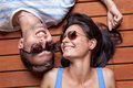 Happy young couple lying on a wooden floor head to head Royalty Free Stock Photos