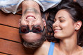 Happy young couple lying on a wooden floor head to head Stock Image