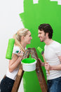 Happy young couple painting their new house bright green standing on a wooden stepladder smiling happily at each other Royalty Free Stock Images