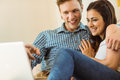 Happy young couple relaxing on the couch with laptop at home in living room Stock Image