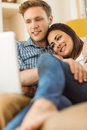 Happy young couple relaxing on the couch with laptop at home in living room Royalty Free Stock Photos