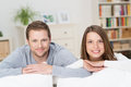 Happy young couple relaxing at home leaning on the back of a sofa smiling the camera Royalty Free Stock Photo