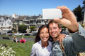Happy young couple in san francisco alamo square taking self portrait photo pictures with smart cell phone camera multiethnic Stock Photos