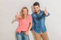 Happy young couple showing the thumbs up gesture leaning on a wall while Royalty Free Stock Photography