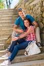 Happy young couple sitting on stairs smiling Stock Images