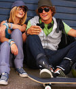 Happy young couple sitting on street Stock Photos