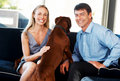 Happy young couple sitting with their pet dog Royalty Free Stock Photo