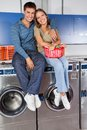 Happy young couple sitting on washing machines portrait of top of in laundry Royalty Free Stock Photos