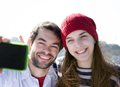 Happy young couple smiling and taking selfie with mobile phone close up portrait of a Royalty Free Stock Images