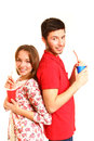 Happy young couple standing back to back and drinking from cups Stock Image
