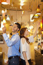 Happy young couple standing back to back while looking at price tag in lights store Stock Photo