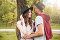 Happy young couple standing and embracing in park Royalty Free Stock Photo