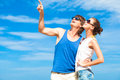 Happy young couple in sunglasses smiling pointing Royalty Free Stock Photos